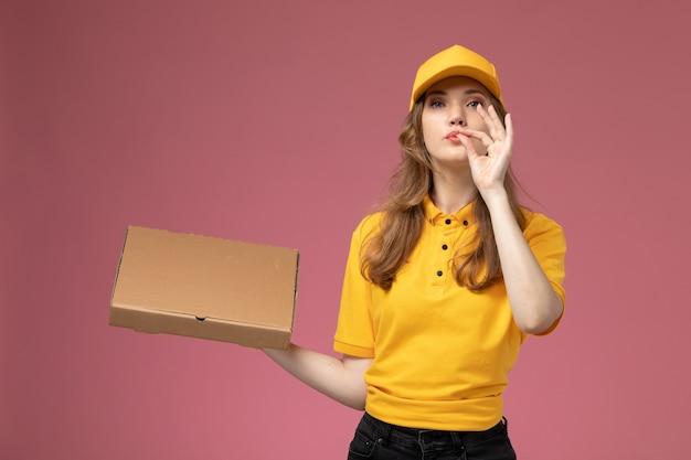 Junge weibliche kurierin der vorderansicht in der gelben uniform, die zustellungsnahrungsmittelbox hält, die auf dem rosa schreibtischjobuniformlieferdienstarbeiter aufwirft