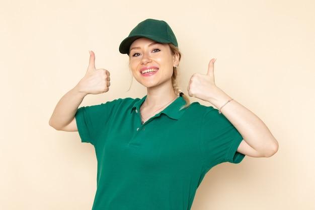 Junge weibliche kurierin der vorderansicht in der grünen uniform und im grünen umhang, die mit lächeln auf dem hellen raumjobmädchen aufwerfen
