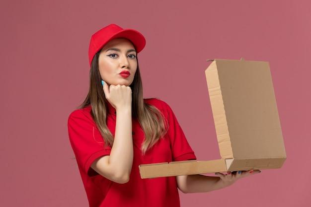 Junge weibliche kurierin der vorderansicht in der roten uniform, die die lieferkiste der lieferung auf rosa hintergrunddienstlieferungsuniform-arbeiterfirma hält