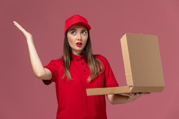 Junge weibliche kurierin der vorderansicht in der roten uniform, die die lieferkiste der lieferung hält und sie auf der hellrosa schreibtischuniform-jobuniformfirma öffnet