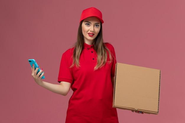 Junge weibliche kurierin der vorderansicht in der roten uniform, die die lieferkiste der lieferung und ihr telefon auf der arbeitsfirma der rosa schreibtischdienstlieferung hält