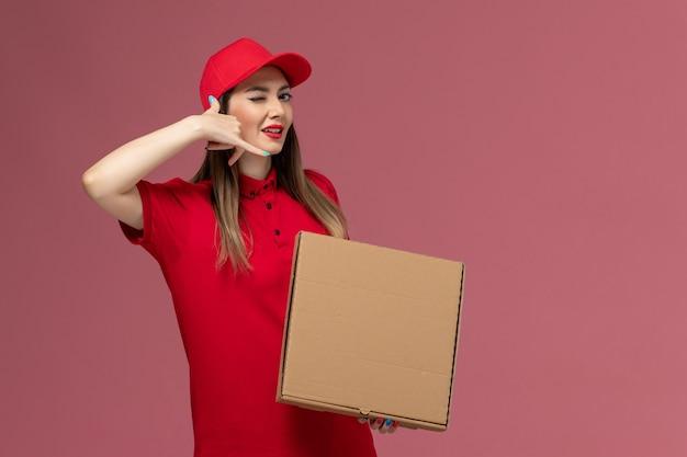 Junge weibliche kurierin der vorderansicht in der roten uniform, die die lieferkost der lieferung hält, die auf der rosa hintergrunddienstlieferungsuniformfirma aufwirft