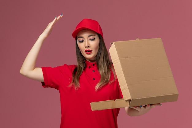Junge weibliche kurierin der vorderansicht in der roten uniform, die die liefernahrungsmittelbox auf dem hellrosa schreibtischdienstlieferungsuniformunternehmen hält