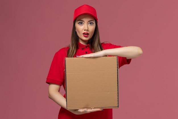 Junge weibliche kurierin der vorderansicht in der roten uniform, die die liefernahrungsmittelbox auf dem rosa schreibtischdienstlieferungsuniformunternehmen hält