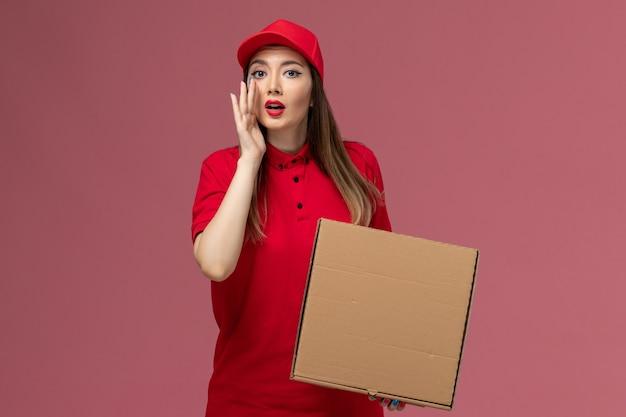Junge weibliche kurierin der vorderansicht in der roten uniform, die die liefernahrungsmittelbox hält, die auf der rosa hintergrunddienstlieferungsuniformfirma flüstert