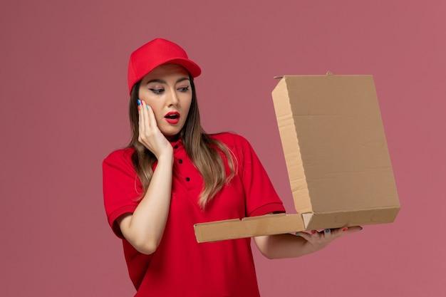 Junge weibliche kurierin der vorderansicht in der roten uniform, die die liefernahrungsmittelbox hält, die sie auf der hellrosa hintergrunddienstlieferungsuniformfirma öffnet