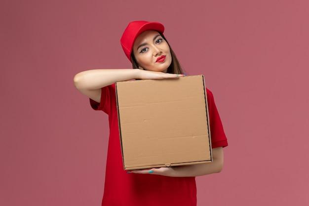 Junge weibliche kurierin der vorderansicht in der roten uniform, die die liefernahrungsmittelbox lächelt, die auf der rosa hintergrunddienstlieferungsuniformfirma lächelt