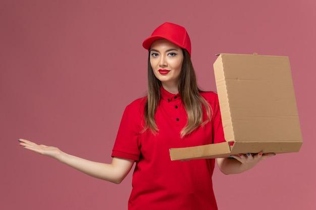 Junge weibliche kurierin der vorderansicht in der roten uniform, die die liefernahrungsmittelbox mit leichter msile auf hellrosa hintergrunddienstlieferungsuniform hält