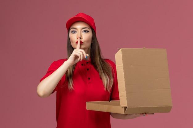 Junge weibliche kurierin der vorderansicht in der roten uniform, die lieferung food box auf hellrosa hintergrund service delivery job uniform firma hält