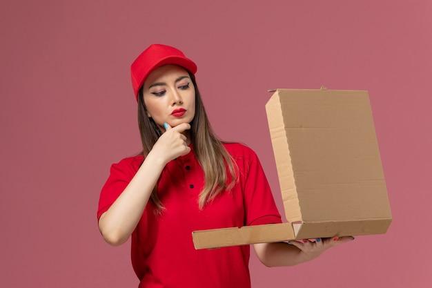 Junge weibliche kurierin der vorderansicht in der roten uniform, die lieferung food box box denkt auf hellrosa hintergrund service delivery job uniform firma denken