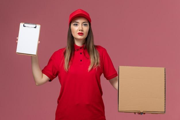 Junge weibliche kurierin der vorderansicht in der roten uniform, die lieferung food box mit notizblock auf dem rosa hintergrund lieferservice uniform firma job hält