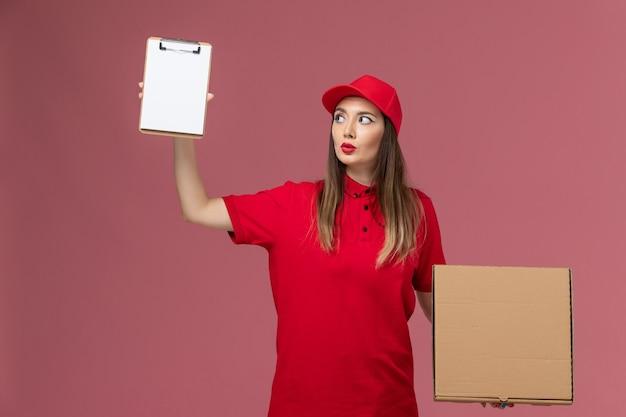 Junge weibliche kurierin der vorderansicht in der roten uniform, die lieferung food box mit notizblock auf hellem hintergrund lieferservice uniform firma job hält