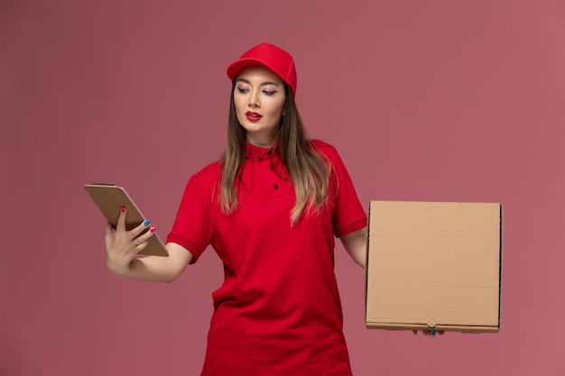 Junge weibliche kurierin der vorderansicht in der roten uniform, die lieferung food box mit notizblock auf rosa boden lieferservice uniform firma job hält