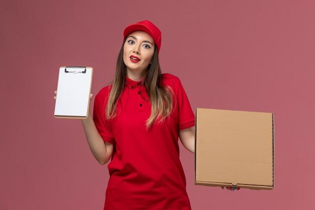 Junge weibliche kurierin der vorderansicht in der roten uniform, die lieferung food box mit notizblock auf rosa hintergrund lieferservice uniform firma arbeiter hält