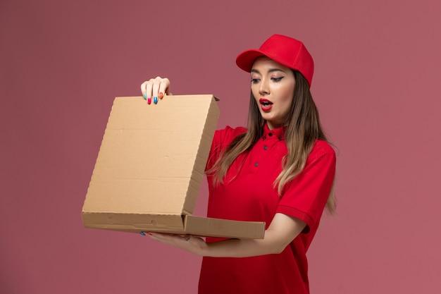 Junge weibliche kurierin der vorderansicht in der roten uniform, die lieferung-nahrungsmittelbox hält, die es auf rosa hintergrunddienstlieferungsjobuniformfirma öffnet