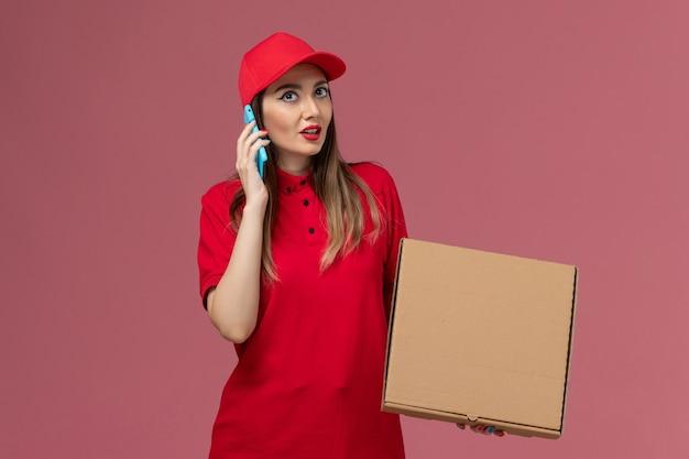 Junge weibliche kurierin der vorderansicht in der roten uniform, die lieferung-nahrungsmittelbox hält, während am telefon auf rosa hintergrundlieferdienstuniformfirma spricht