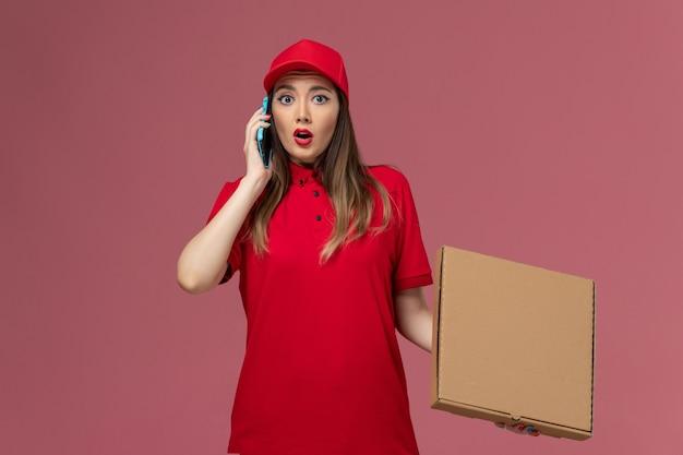 Junge weibliche kurierin der vorderansicht in der roten uniform, die zustellungsnahrungsmittelbox hält, während am telefon auf hellrosa hintergrundlieferdienstuniformfirma spricht