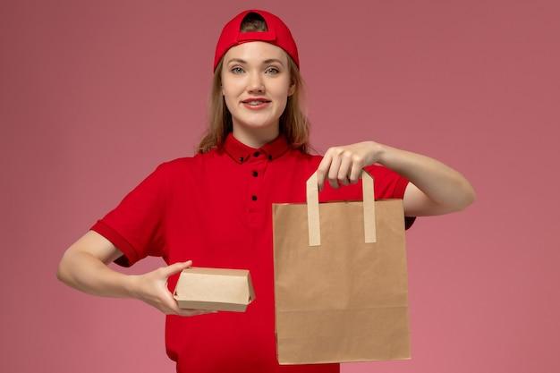 Junge weibliche kurierin der vorderansicht in der roten uniform und im umhang, die liefernahrungsmittelpakete an der rosa wand halten
