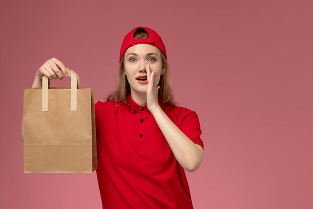 Junge weibliche kurierin der vorderansicht in der roten uniform und im umhang, die lieferung-nahrungsmittelpaket halten, das auf rosa wand ruft