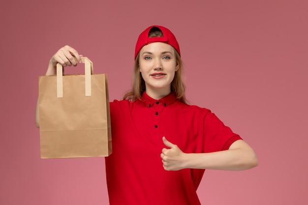 Junge weibliche kurierin der vorderansicht in der roten uniform und im umhang, die lieferung-nahrungsmittelpaket lächelnd auf rosa wand halten