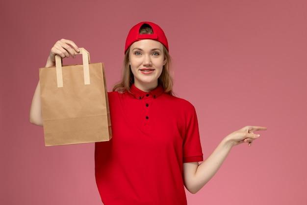 Junge weibliche kurierin der vorderansicht in der roten uniform und im umhang, die lieferung-nahrungsmittelpaket mit lächeln auf rosa wand halten