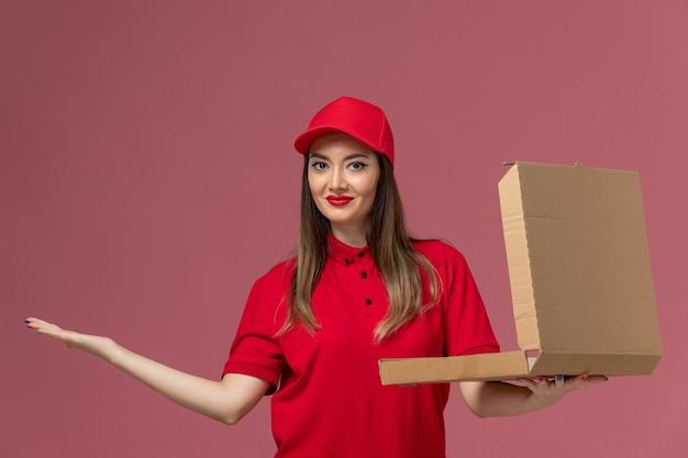 Junge weibliche kurierin der vorderansicht in roter uniform, die lieferung food box auf hellrosa boden service lieferung job uniform firma hält