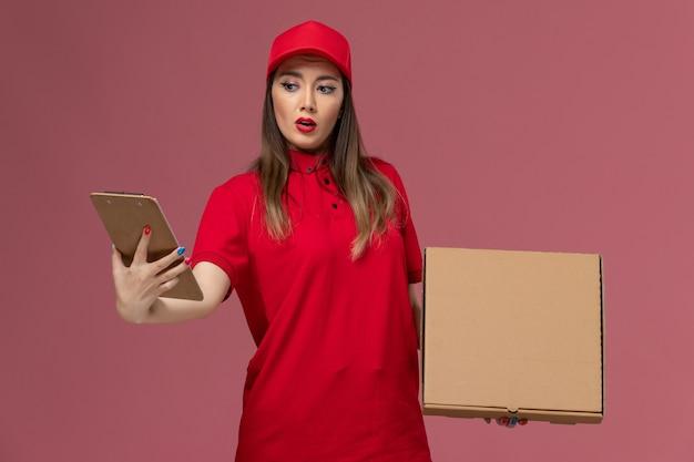 Junge weibliche kurierin der vorderansicht in roter uniform, die lieferung food-box mit notizblock auf rosa hintergrund lieferservice uniform job firma hält