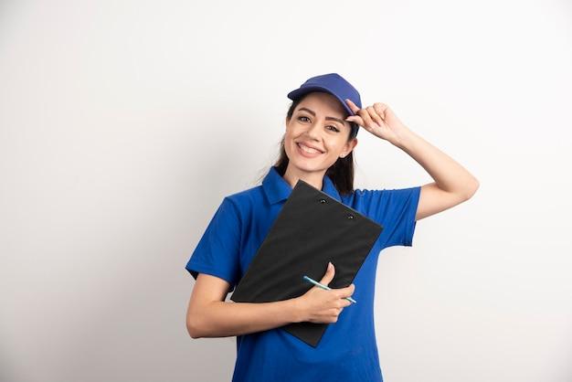 Junge weibliche kurierin in blau scheuert mit einer zwischenablage. foto in hoher qualität