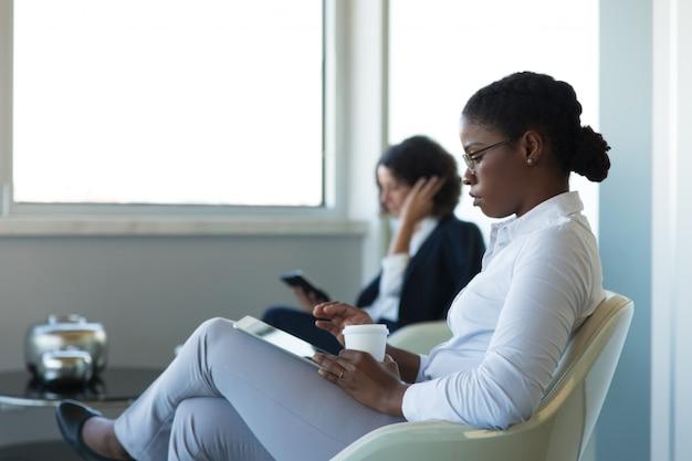 Junge weibliche managerlesenachrichten auf tablette