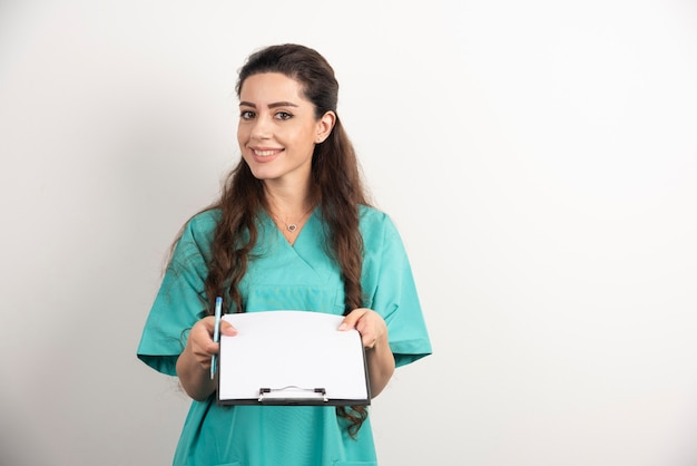 Junge weibliche medizinische angestellte, die krankenakten halten.