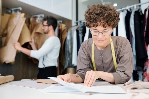 Junge weibliche näherin oder modedesignerin, die skizze des neuen modells durch arbeitsplatz im studio betrachtet