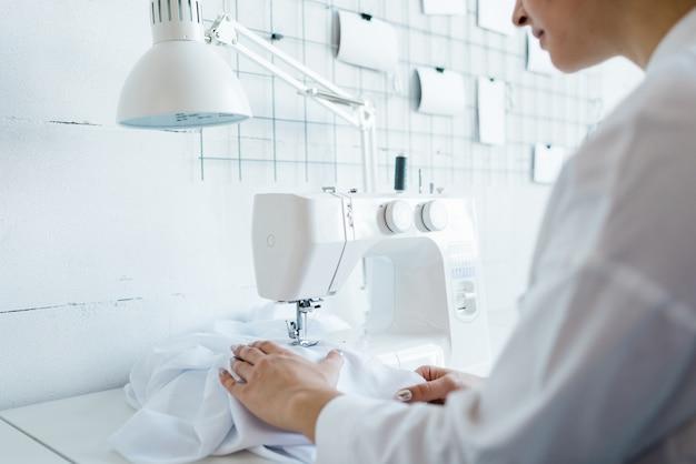 Junge weibliche nähfabrikarbeiterin in weißer arbeitskleidung, die durch elektrische maschine sitzt, während neue kleidung schafft