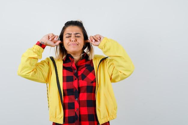 Junge weibliche ohren mit fingern in kariertem hemd, jacke und genervt aussehen. vorderansicht.
