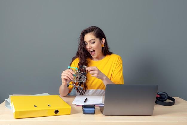 Junge weibliche online-shop-manager sitzt an einem schreibtisch und arbeitet mit einem laptop und dokumenten,