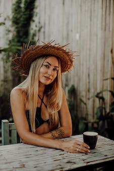 Junge weibliche person mit strohhut sitzt am tisch und betrachtet die kamera mit kaffeetasse im café in thailand in ihren ferien.