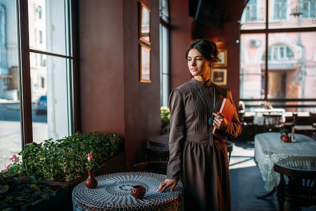 Junge weibliche person steht innerhalb des cafés