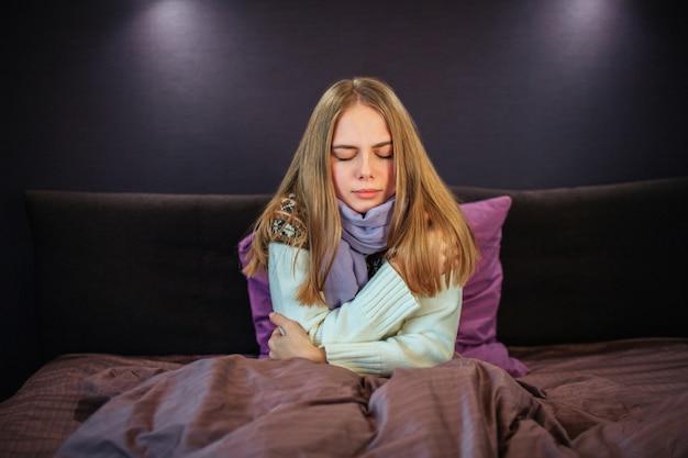 Junge weibliche person wurde kalt. sie trägt einen weißen pullover und einen blauen schal. junge frau ist krank. sie hält die augen geschlossen. mädchen kann nicht genug wärme bekommen.