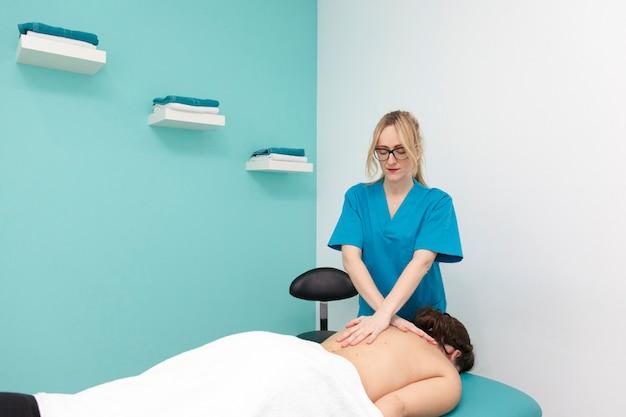 Junge weibliche physiotherapeutin, die mit therapeutischer massage arbeitet