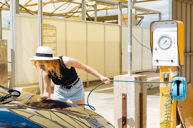 Junge weibliche pumpende autoreifen an der tankstelle