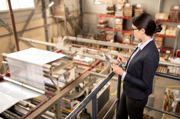 Junge weibliche qualitätskontrollexpertin mit touchpad, die neue industrieanlagen in der chemischen produktionsfabrik testet