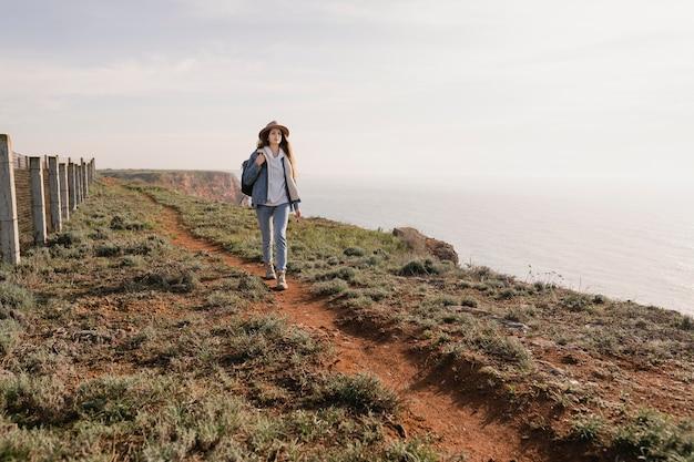 Junge weibliche reisende, die den frieden um sie herum genießt