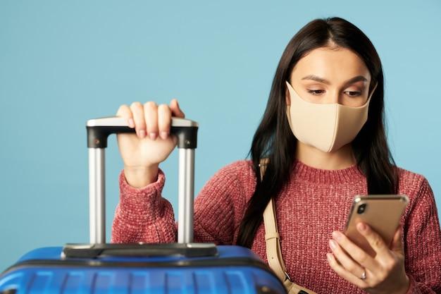 Junge weibliche reisende, die nachricht auf dem smartphone lesen