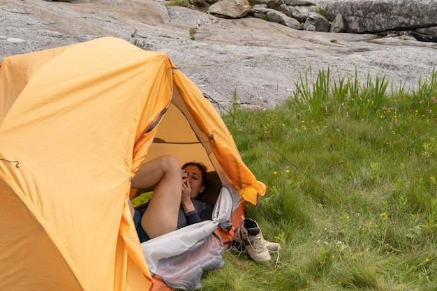 Junge weibliche reisende lächelnd im zelt liegend