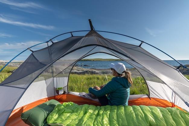 Junge weibliche reisende sitzen in ihrem zelt und bewundern die landschaft am strand
