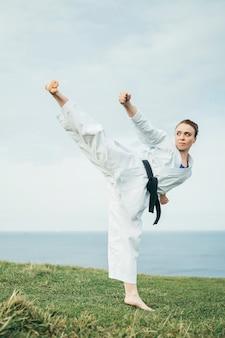 Junge weibliche rothaarige karate-athletin, die einen hohen tritt trifft