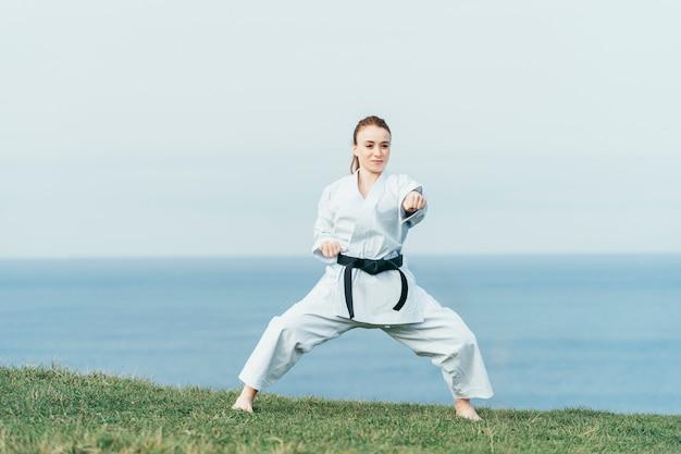 Junge weibliche rothaarige karatekämpferin, die einen linken schlag trifft