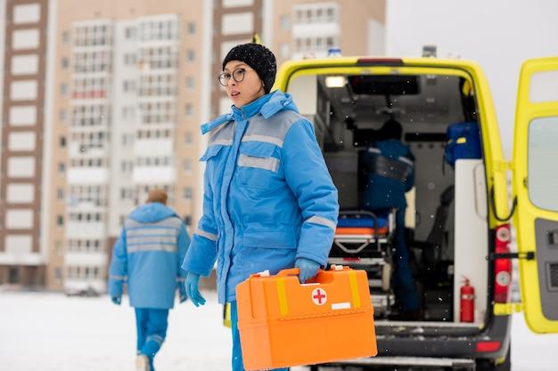 Junge weibliche sanitäterin in blauer arbeitskleidung, die erste-hilfe-ausrüstung trägt, während sie zu einer kranken person im freien am wintertag eilt