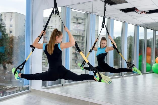 Junge weibliche sportler, die übungsbeine mit trx-trägern in der turnhalle trainieren. sprt für gesundheit.