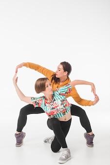 Junge weibliche tänzer, die gegen weißen hintergrund aufwerfen