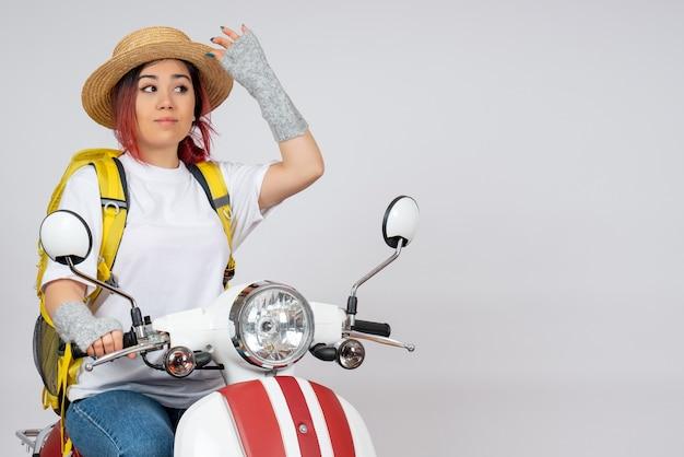 Junge weibliche touristin der vorderansicht, die auf motorrad auf fotofahrt des touristenfahrzeugs der weißen wandgeschwindigkeitsfrau sitzt